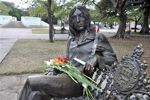 Người hâm mộ đặt hoa tưởng niệm lên bức tượng của John trong công viên.