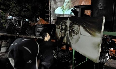 Các nghệ sĩ Cuba khắc họa chân dung John lên bức tranh lớn trưng bày trong công viên.