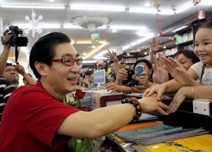 Trong đám đông khám giả, một em bé gái (phải) phải nhờ người người nhà nâng lên để vươn người ra bắt tay với ông Tôn Ngộ Không. Ảnh: Thoại Hà.