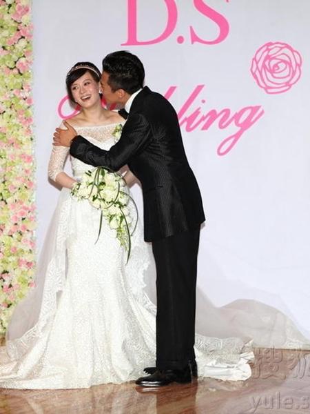 Chú rể âu yếm hôn cô dâu trước ống kính của giới truyền thông.