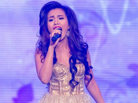 """Phương Vy tươi tắn trong ca khúc """"Nắng theo chân em"""" và """"Cô gái Việt"""". Cô diện một bộ váy xòe lấp lánh, phong cách trang điểm sang trọng với mái tóc ngang vai uốn xoăn nhẹ, son môi đỏ, trông nữ ca sĩ có vẻ già hơn tuổi."""